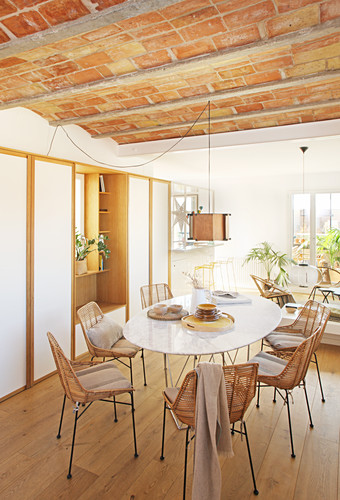 Wicker chairs at oval dining table below vaulted ceiling