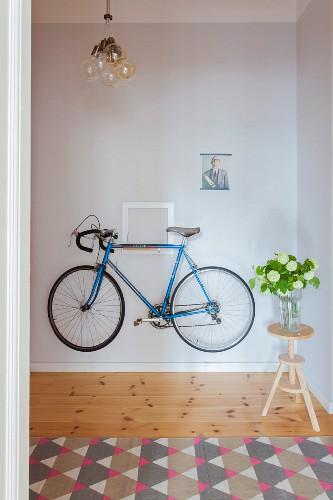 Blue bike hung on hallway wall next to flowers on stool