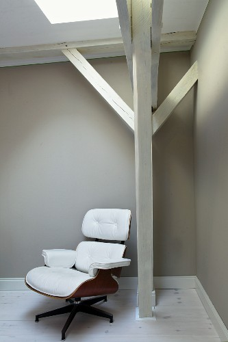 Eames Lounge Chair upholstered in white leather below wooden beam structure