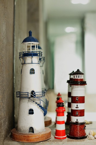 Three lighthouse ornaments in front of mirror