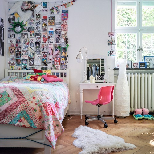 Patchwork quilt on bed, desk and chair and collection of photos decorating wall in girl's bedroom