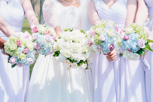 Bride and bridesmaids dressed in white holding beautiful bouquets
