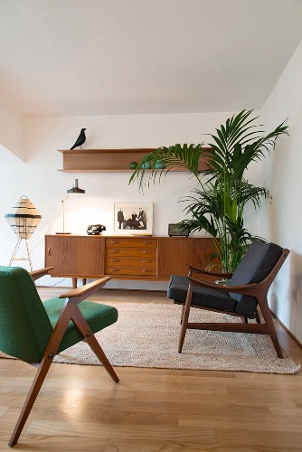Retro armchair in front of sideboard and potted palm in living room