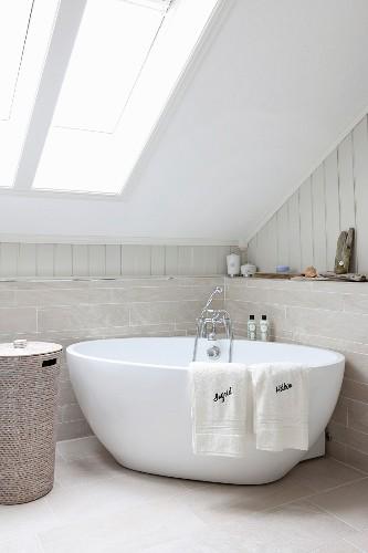 Free-standing bathtub below skylight in sloping ceiling