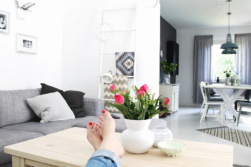 Woman's feet propped next to vase of red tulips on wooden couch table