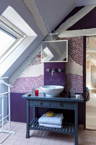 Wooden roof beams in lilac and violet attic bathroom