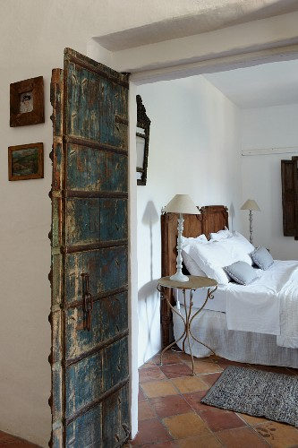 Bed with wooden headboard and white bed linen next to lamp on delicate bedside table in rustic bedroom