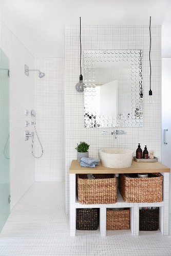 Tiled washstand with storage baskets and countertop sink and view into accessible shower area