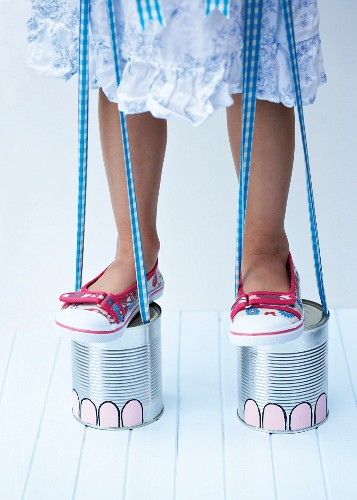 Stilts painted to look like elephant feet hand-made from tin cans and ribbon