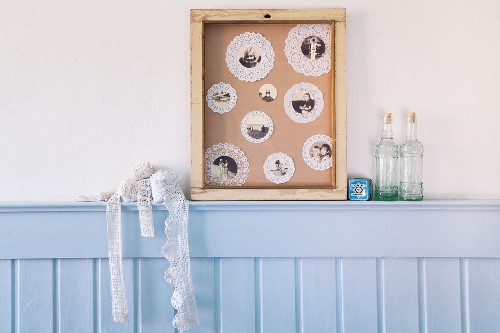 Collage on paper doilies in wooden frame