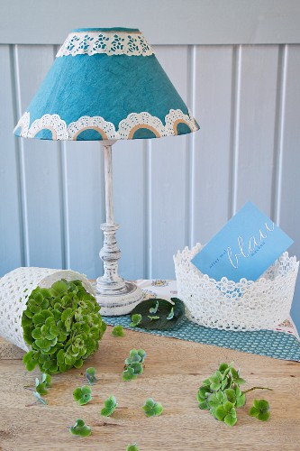 Lampshade decorated with paper doily between lace baskets