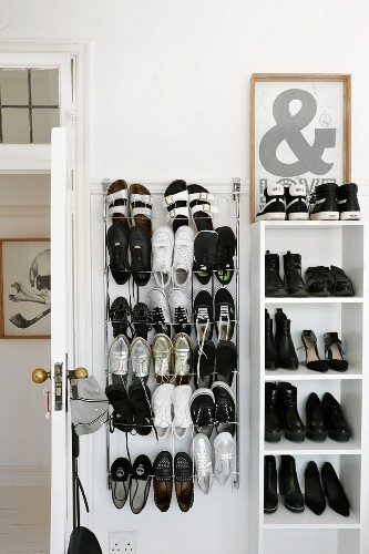 Shoes on shelves and wire rack behind white interior door in period apartment