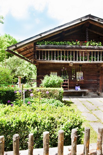 Rustic log cabin with balcony and garden in early summer