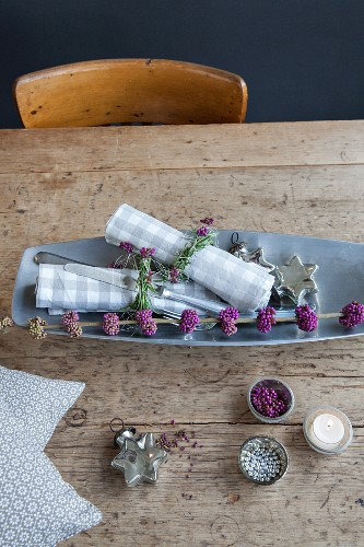 Branch of purple beautyberry and checked linen napkins with rosemary napkin rings on wooden table