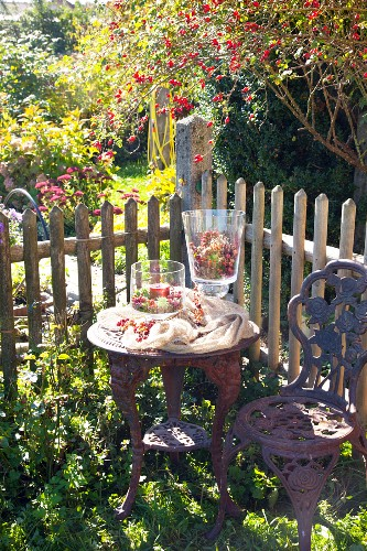Autumnal arrangement with candle lantern on ornate table in garden