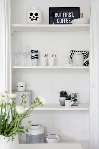 Black and white crockery and cacti on shelves in niche