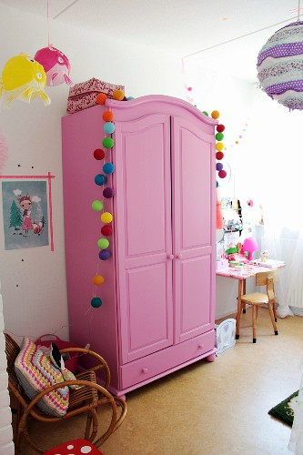 Pink wardrobe decorated with colourful garlands in girl's bedroom