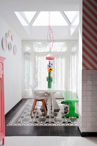 White table, green bench and shell chairs on black and white tiled floor under skylight