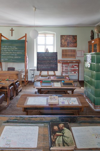 Blackboards, vintage school desks and open schoolbooks in classroom in school museum