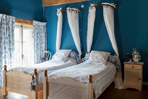 Twin beds with white bed crowns on blue wall in bedroom