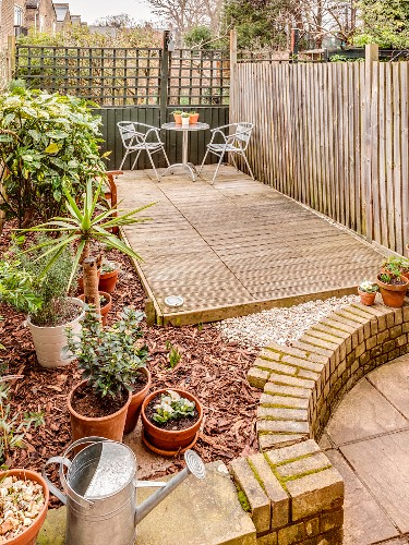 Wooden terrace and screen in back courtyard garden