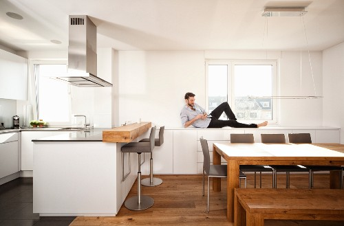 Man lying on counter in open-plan kitchen using smartphone