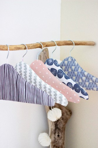 Fabric-covered coathangers on branch used as clothes rack