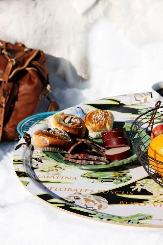Cinnamon swirls and sliced sausage on tray