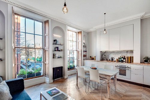 Fitted kitchen, dining table and sofa in open-plan interior of renovated townhouse apartment