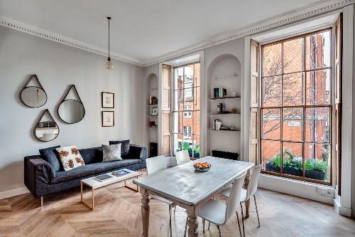 Offener Wohnraum mit Esstisch und Sofa in renovierter Stadtwohnung