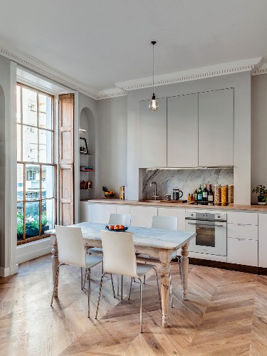 Dining table and chairs in front of fitted kitchen in renovated townhouse apartment