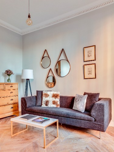 Three mirrors above grey sofa and coffee table in renovated townhouse apartment