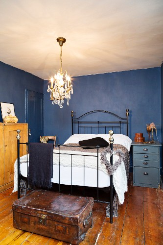 Metal bed in small bedroom with blue walls and old wooden floor