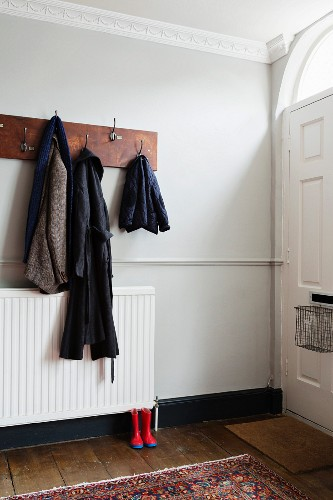 Coat rack made from old plank in hallway with dado rail and stucco frieze