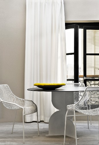 Designer table and metal chairs in front of long curtains on French windows leading to roof terrace