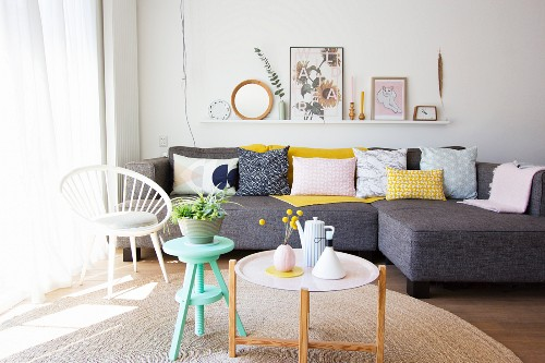 Stool and tray table in front of grey sofa with pastel scatter cushions