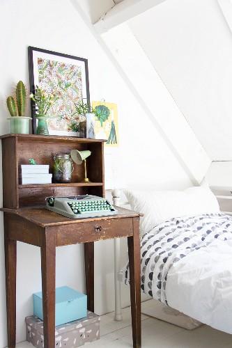 Typewriter on old writing desk next to bed below sloping ceiling