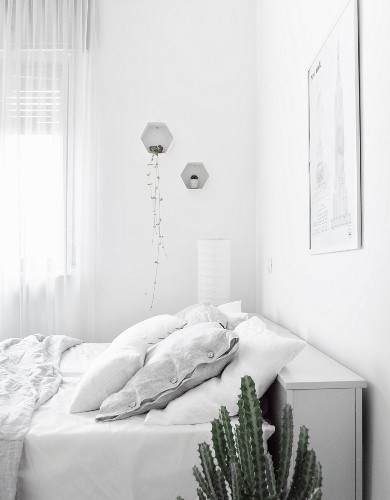 Bed with storage in headboard in white bedroom
