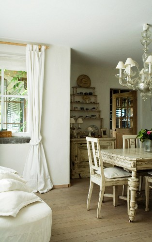 Wooden floor and chandelier in dining area of renovated country house