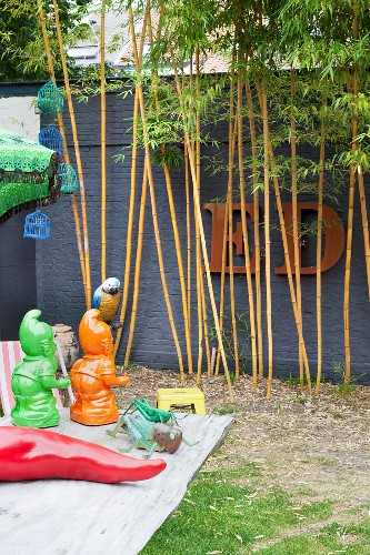 Colourful ornament in garden with arrangement of bamboo and ornamental letters on wall