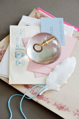 A DIY paperweight made of artificial resin with a nostalgic cast-metal key on a pile of letters