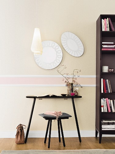 A black table with a stool and a bookcase in front of an elegant wall design with plastered mouldings and pastel-coloured non-woven wallpaper
