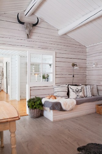 Comfortable couch in wintry wooden house