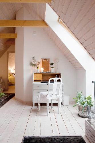 White bureau below wood-clad sloping ceiling