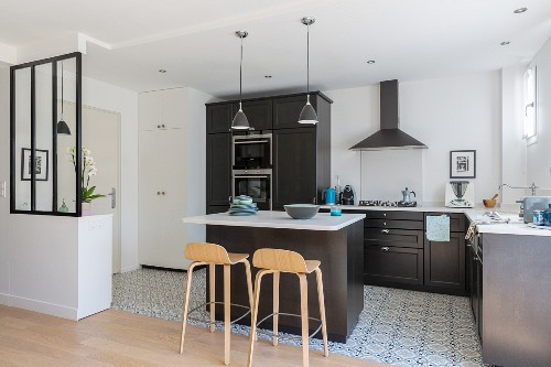 Black fitted kitchen with white worksurface in bright apartment