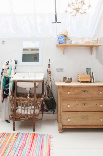 Chest of drawers next to sink with vintage laundry basket below in feminine bathroom