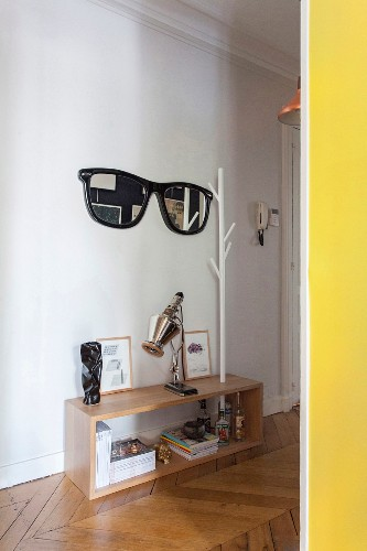 Yellow door frame and view of mirror shaped like sunglasses with black frame next to white coat rack in hall