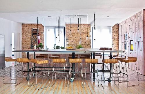 Designer bar stools at long dining table on castors in open-plan interior