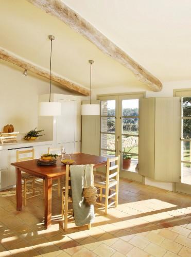 Sunlight falling on dining table through tall lattice French windows