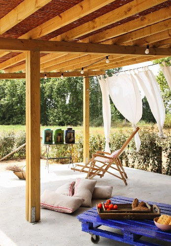 Wooden deckchair, pallet table and floor cushions on roofed terrace